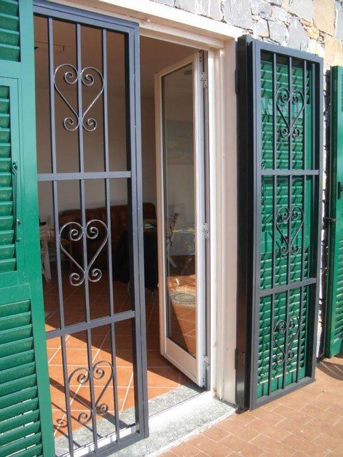 una griglia in ferro in una finestra con delle persiane verdi