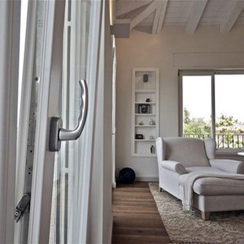 una maniglia di una finestra e sulla destra un salotto