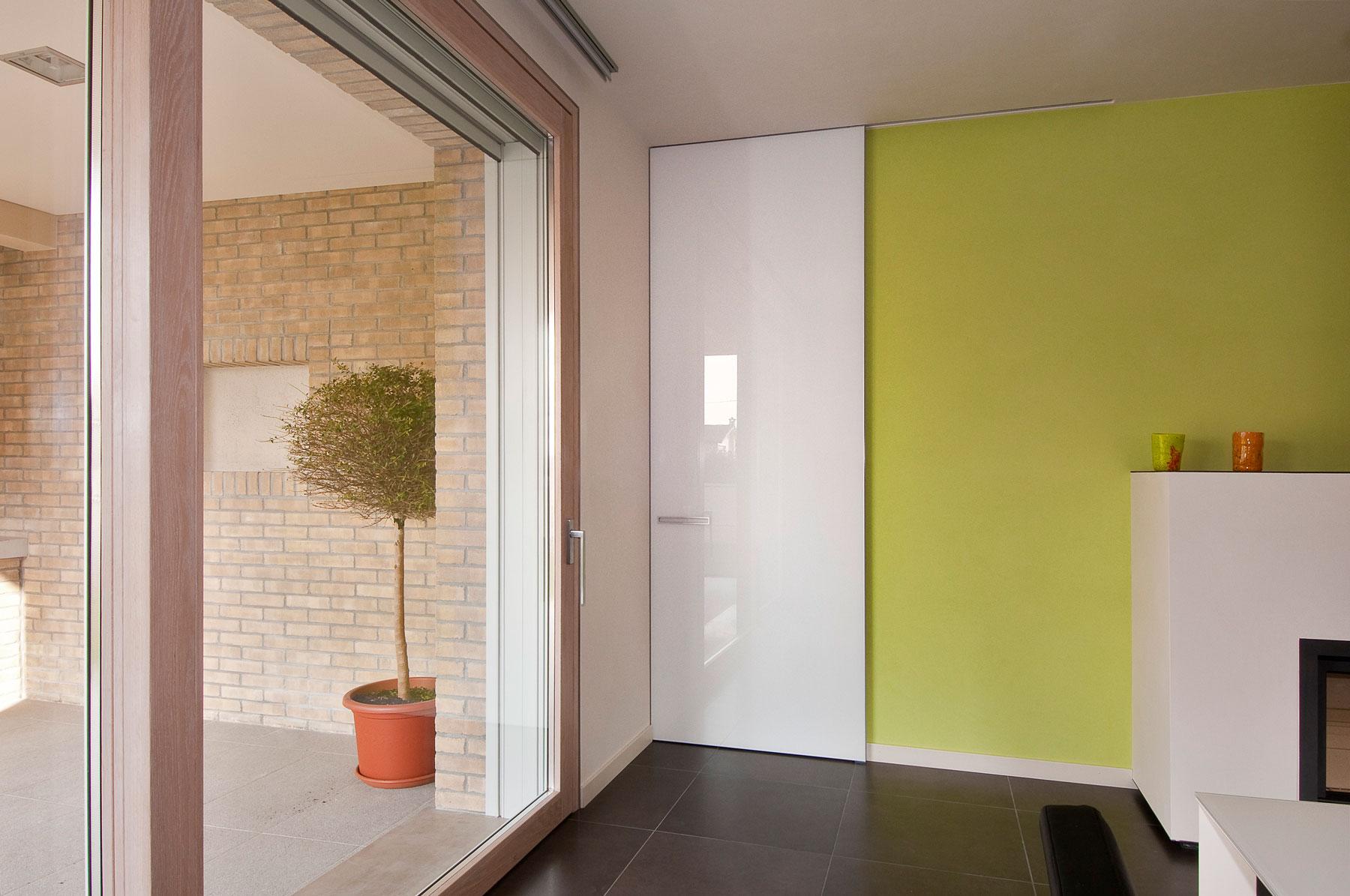 una stanza con una porta sulla sinistra e un balcone con una pianta