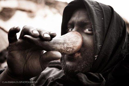 Uomo con viso dipinto di nero beve da un corno
