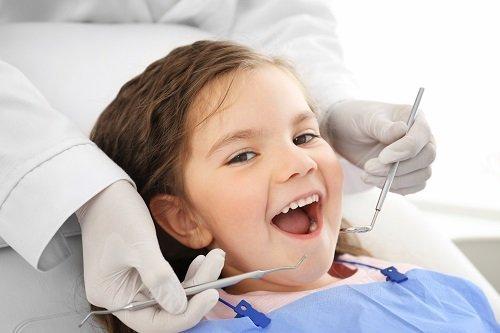 due mani con degli strumenti dentistici e una bambina con la bocca aperta
