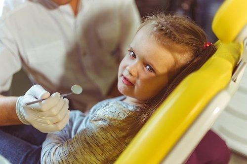 una bambina sdraiata è una mano con uno specchietto