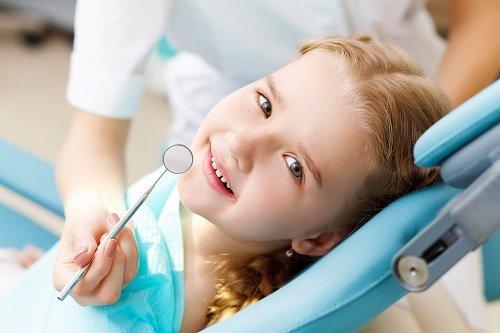 una bambina sorridente e una mano con uno specchietto
