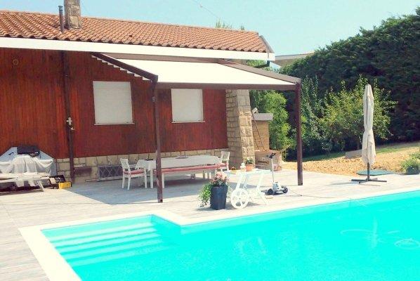 una piscina, accanto una struttura con una tenda da sole e sotto un tavolo