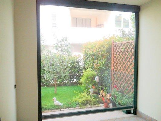 una vetrata e vista di una prato e delle piantine
