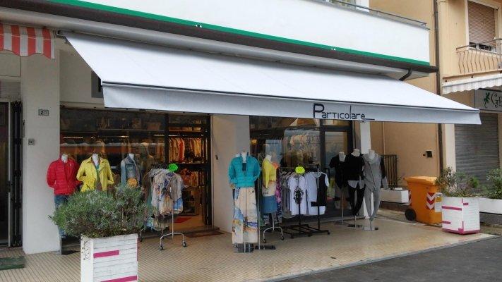 vista dall'esterno di un negozio di abbigliamento con una tenda da sole grigia