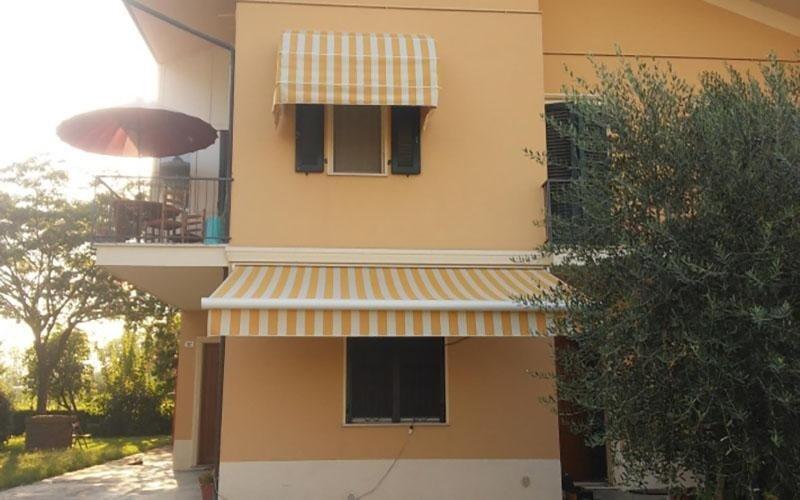 due finestre di uno stabile con delle tende da sole a righe bianche e gialle