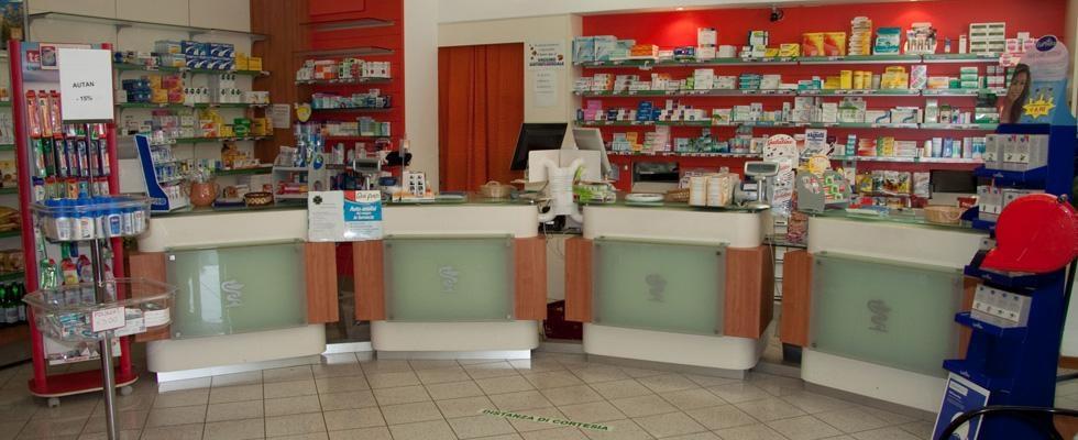 un bancone a curva e dietro delle mensole con delle medicine