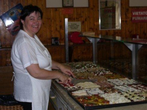 una donna dietro a un bancone mentre farcisce delle pizze in teglia