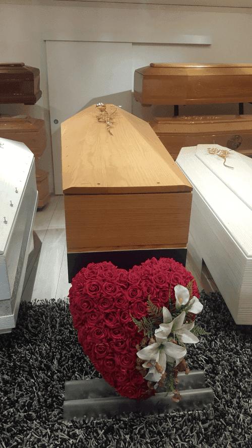 Primo piano di un cuore fatto di rose con gigli bianchi su un lato e una bara in legno chiaro con un dettaglio di un fiore metallizzata sopra