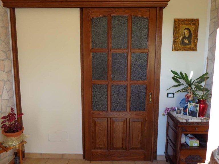 immagine di una porta con vicino un comodino