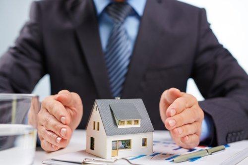 uomo con tra le mani una casa in miniatura