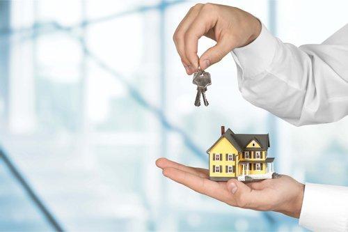uomo con chiavi e una casa in miniatura in mano