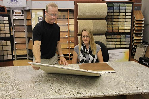 Professional showing the range of flooring option to the women in  Chesterfield, MO