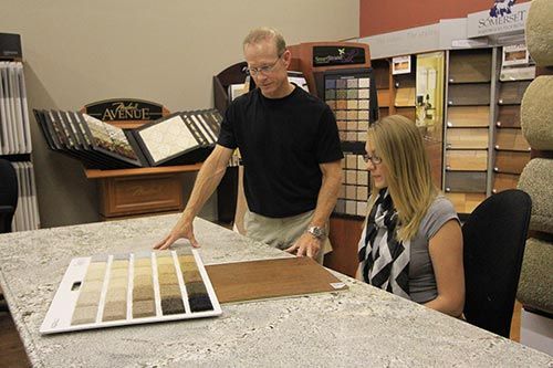 Expert showing the flooring option in the showroom in Chesterfield, MO