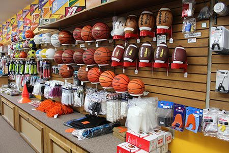 A shelf with various different sports balls
