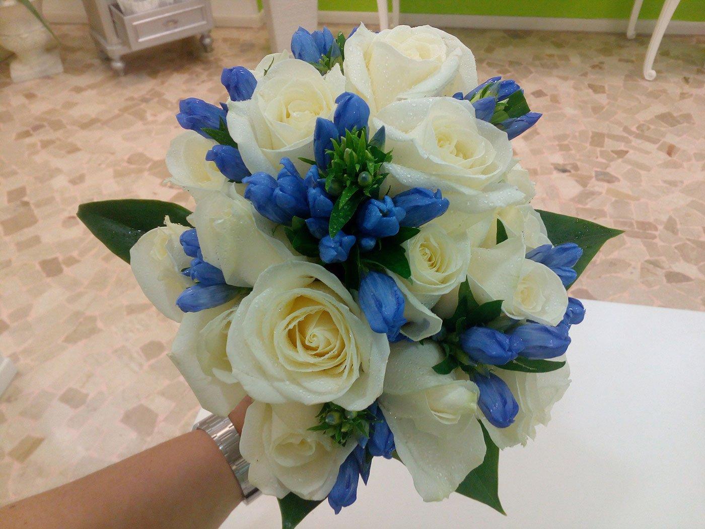 una mana che tiene un mazzo di fiori blu e rose bianche