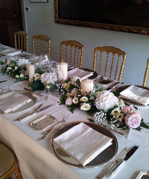 tavola apparecchiata con piatti e posate d'argento,dei fiori al centro e sedie dorate