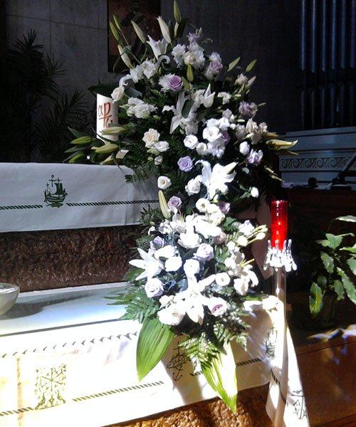 una corona di rose accanto a una bara e sulla destra una candela rossa