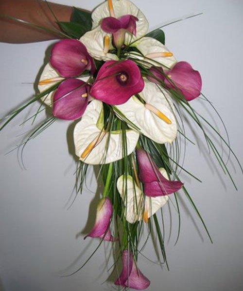 una mano che sorregge un bouquet di fiori rosa e bianchi