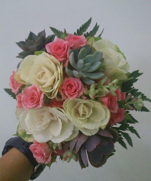 una mano con un orologio al polso che sorregge un bouquet con foglie di piante grasse e rose rosa, bianche e gialle