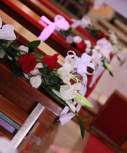 mazzi di rose rosse e bianche su una panca in legno di una chiesa