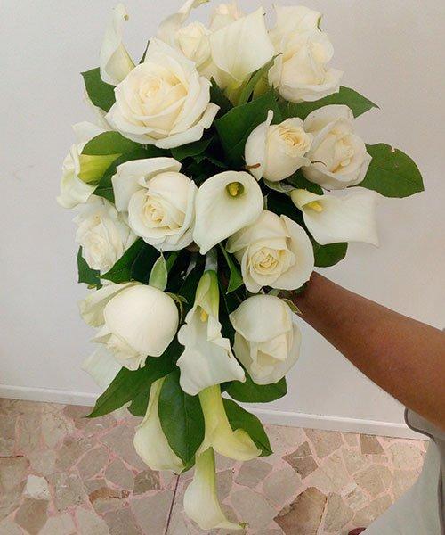 una mana che tiene un mazzo di fiori bianchi e rose bianche