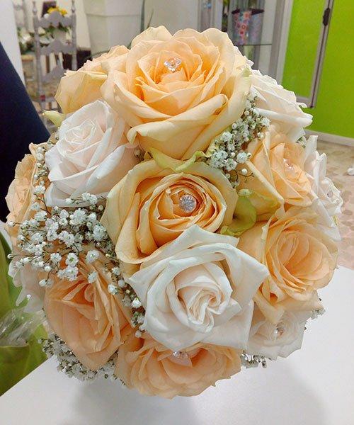 un mazzo di rose bianche,arancioni e piccoli fiorellini bianchi