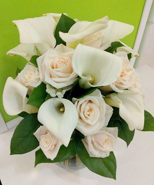 composizione di rose rosa, altri fiori bianchi e delle foglie verdi