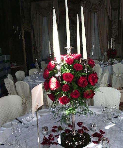 composizione di rose rosse in un vaso d'argento su un tavolo di un ristorante elegante