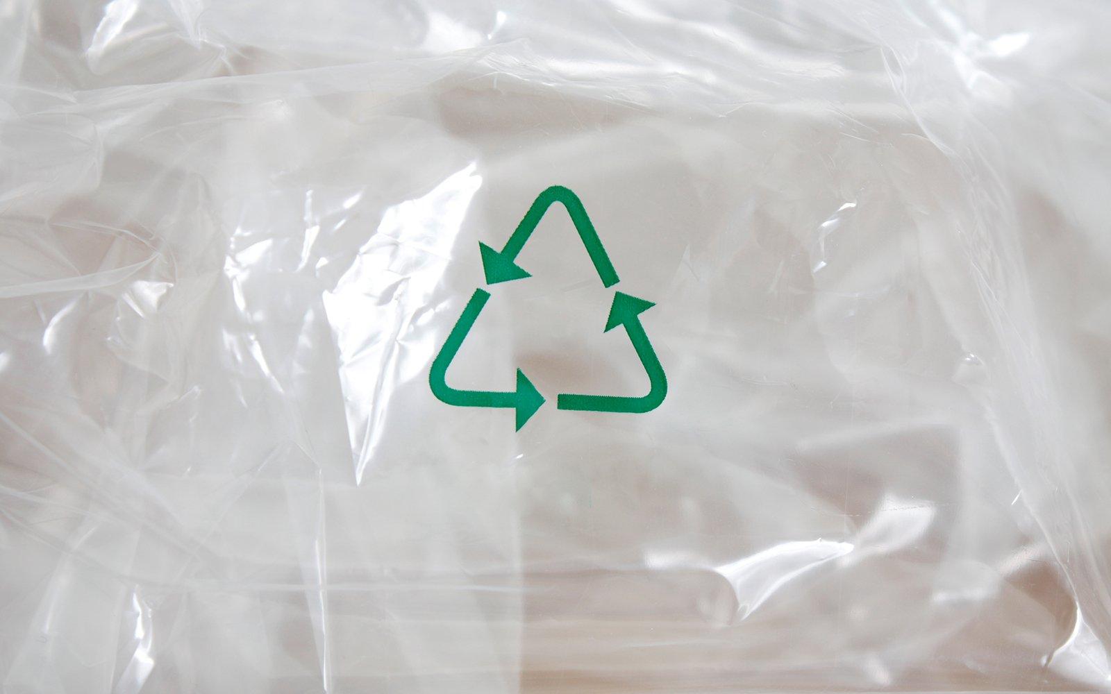 non simbolo verde di riciclo e dietro un sacchetto di plastica