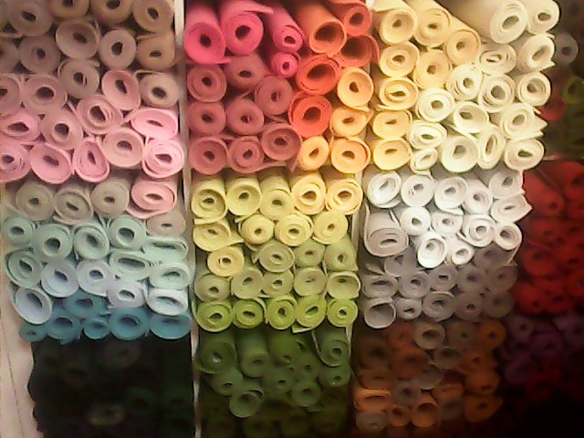Mucchio dei tessuti variopinti sugli scaffali di un negozio