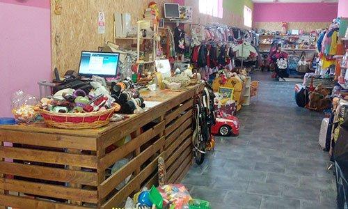 un negozio di articoli per bambini con giocattoli e sulla sinistra una scrivania a forma di cassa di legno con un monitor