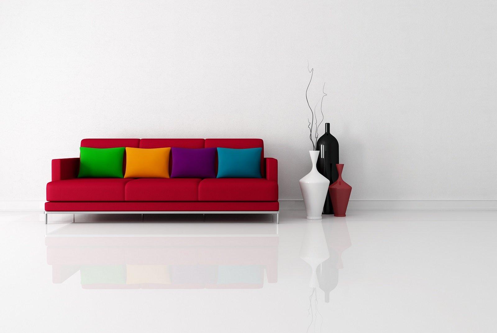 Sofà rosso, cuscini verde,giallo,lila e blu, tre vasi nero,bianco e rosso