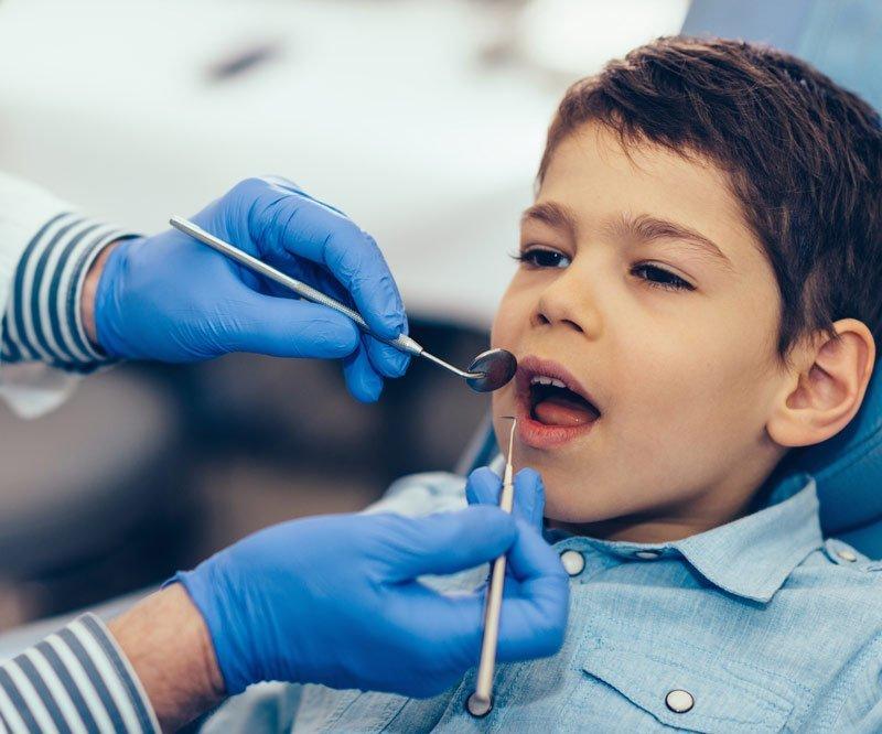 boy getting teeth examined