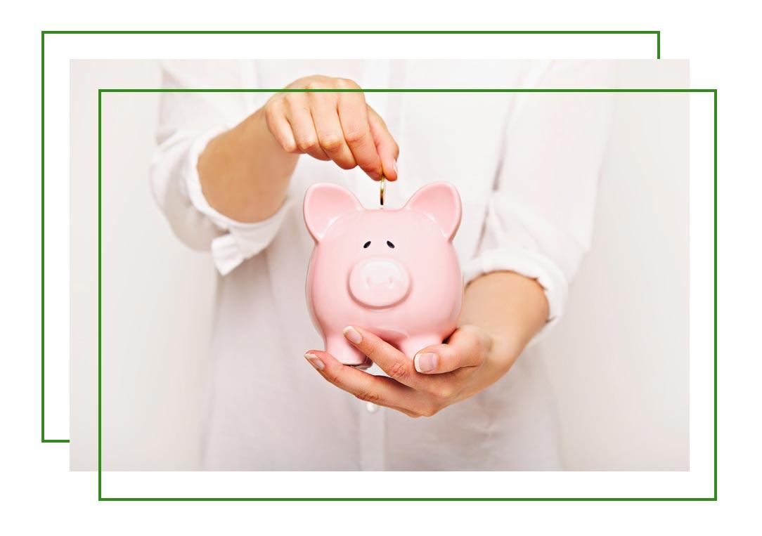 a person dropping money into a piggy bank