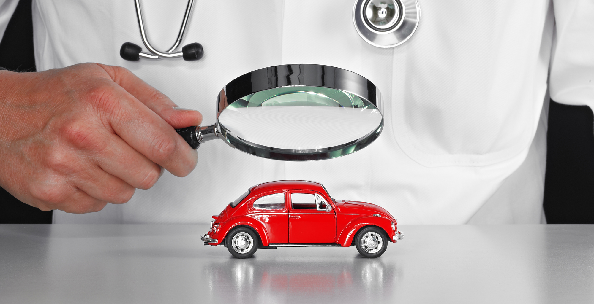 A car doctor looking at a red car model through a magnifying glass