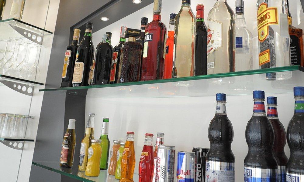 delle bottiglie di liquore su delle mensole di vetro