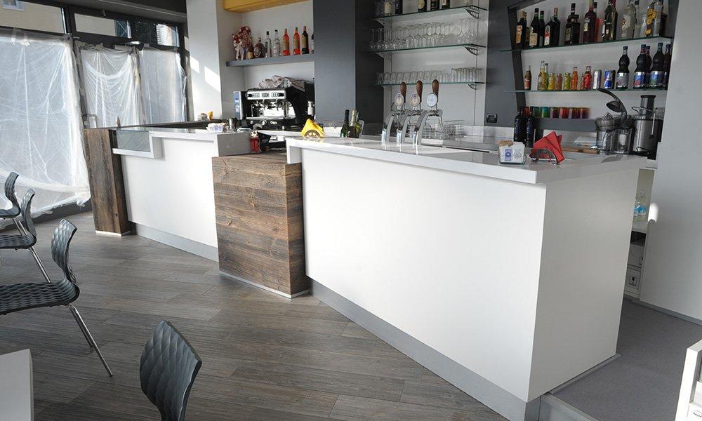interno di un bar con bancone bianco e marrone e vista della macchina del caffè e dei liquori