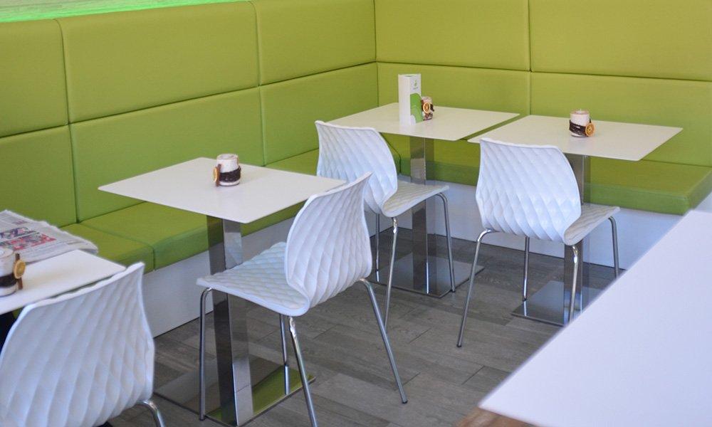 dei tavoli e delle sedie di color bianco e panche di color  verde