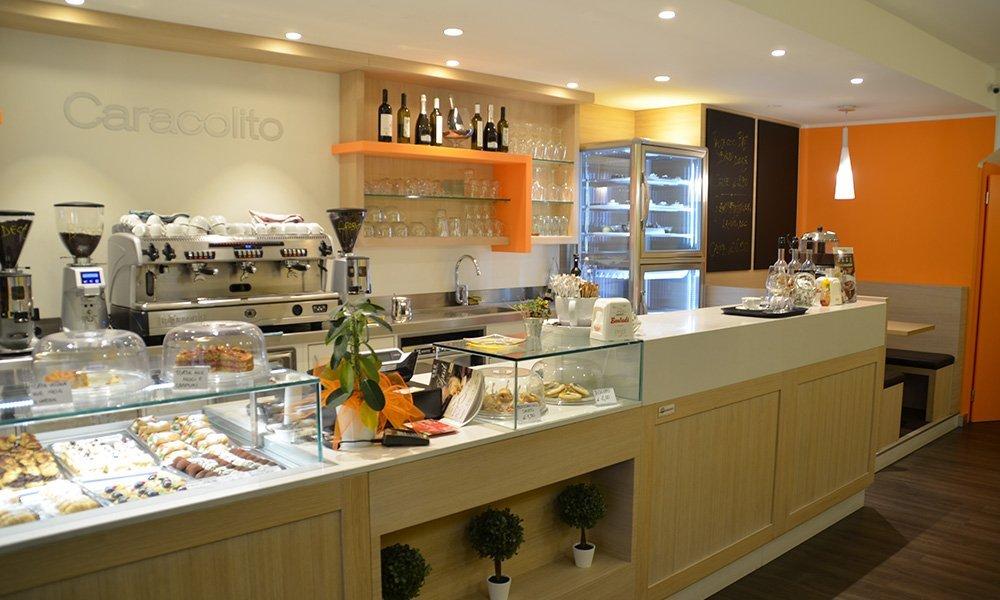 interno di un bar pasticceria con vetrine di dolci e macchina del caffè
