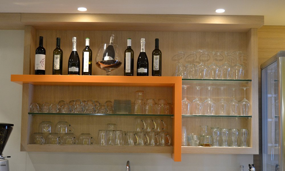 delle mensole con bicchieri e bottiglie