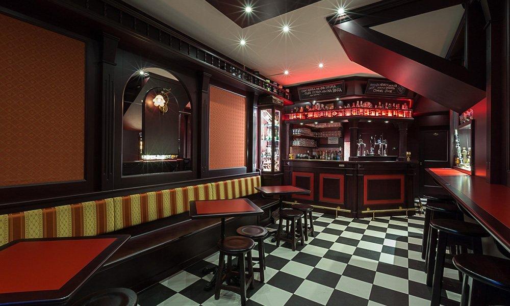interno di un locale con mobili in legno scuro e di color rosso