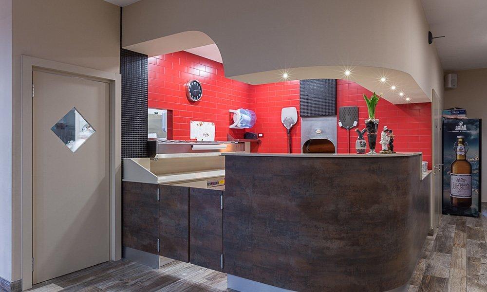 interno di una pizzeria con vista del forno e delle piastrelle rosse