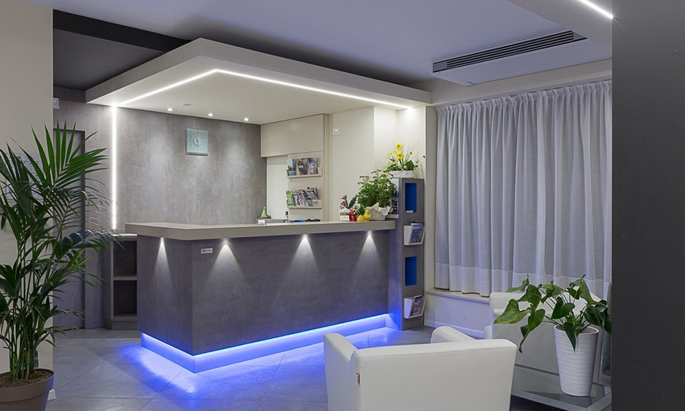 un bancone grigio con luci blu e dei divanetti con accanto dei vasi con delle piante