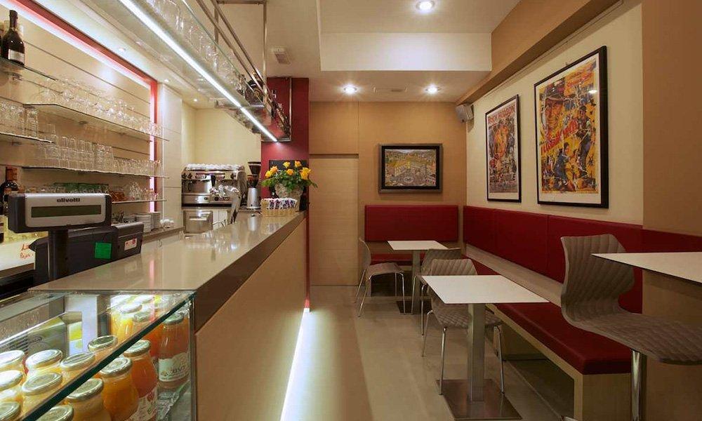 interno di un bar con vista del bancone, dei quadri a muro e dei tavoli con le sedie
