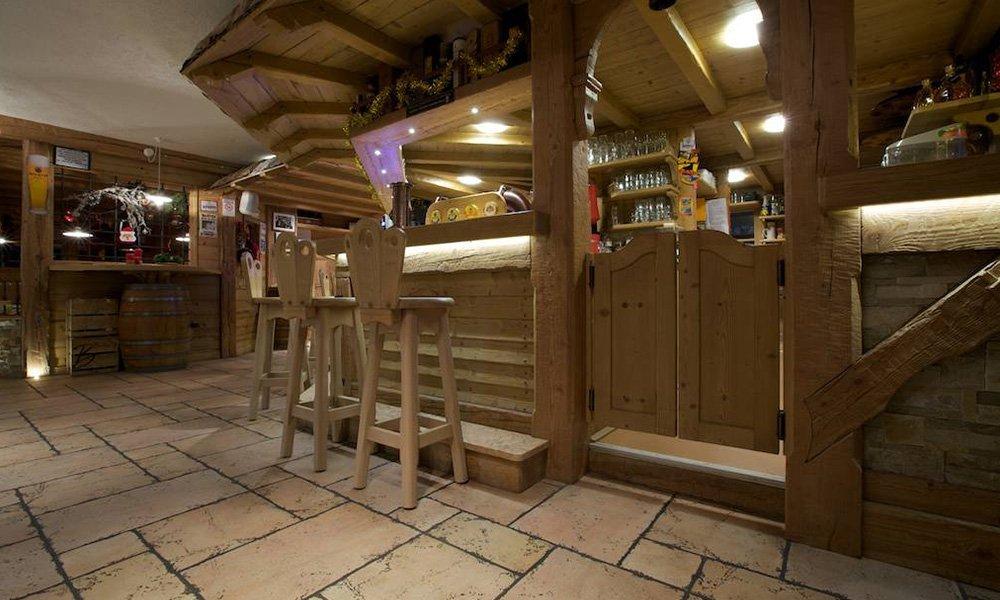 un locale con degli sgabelli in legno e una porta a due antine in legno