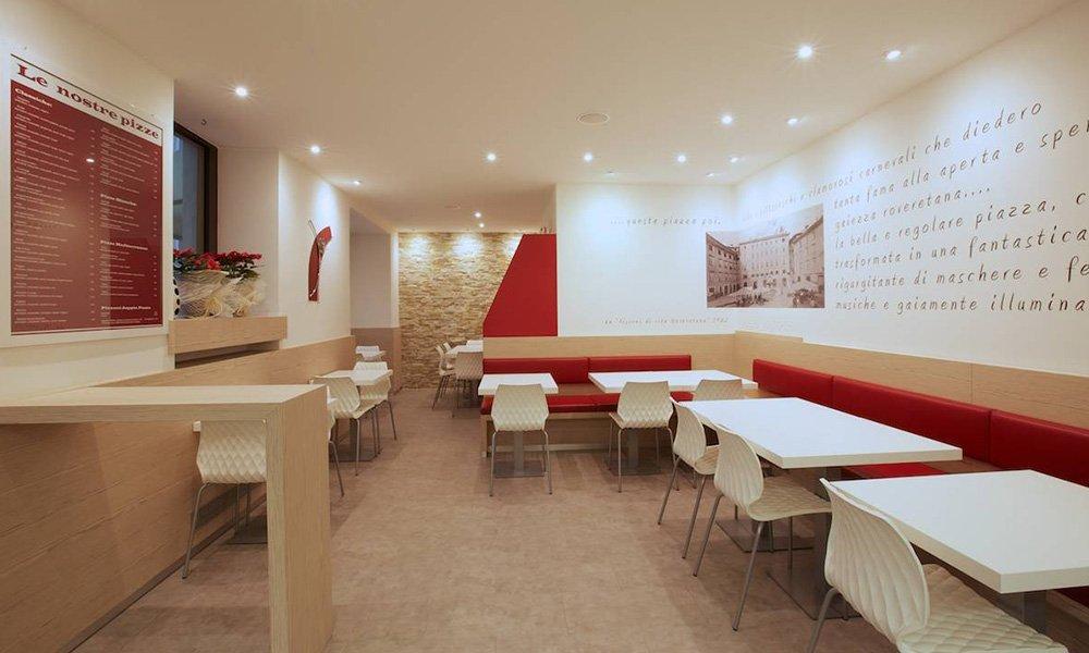 interno di un locale con tavoli, sedie bianche e  panche di color rosso