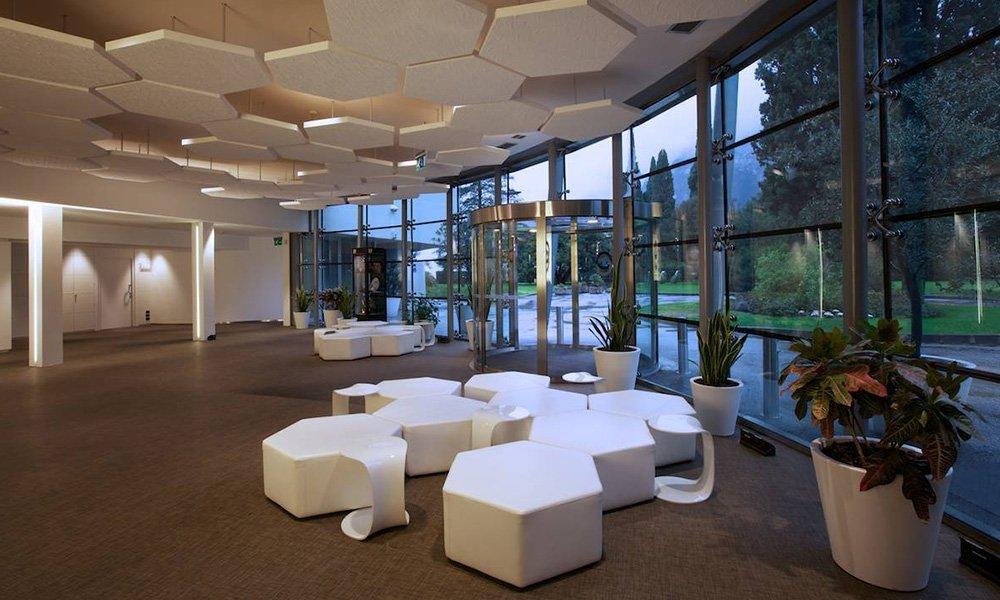 dei pouf moderni di color bianco all'ingresso di un edificio con vasi di piante e vetrate a vista