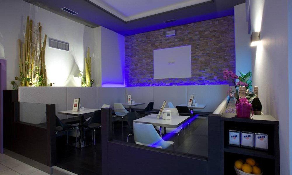 lista dei tavoli e delle sedie in un locale con una parete di pietra e luci blu